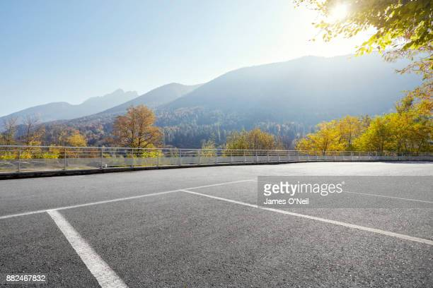 empty parking area with distant hills on sunny day - parkfläche stock-fotos und bilder