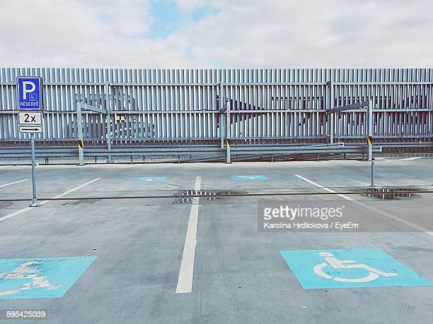empty parking lot against sky - disabled sign stock photos and pictures