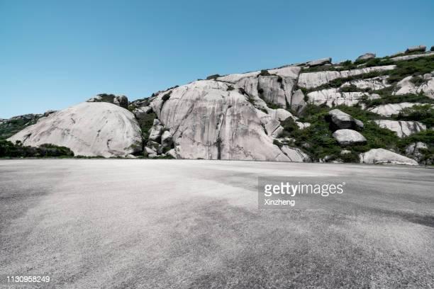 empty parking lot front of mountain ranges, stone texture for background - front view photos et images de collection