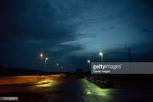 empty parking lot in iceland with street lights reflected on wet road - empty lot night stock pictures, royalty-free photos & images