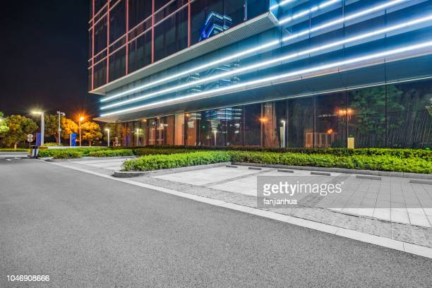 empty parking lot outside office building at night - empty lot night stock pictures, royalty-free photos & images