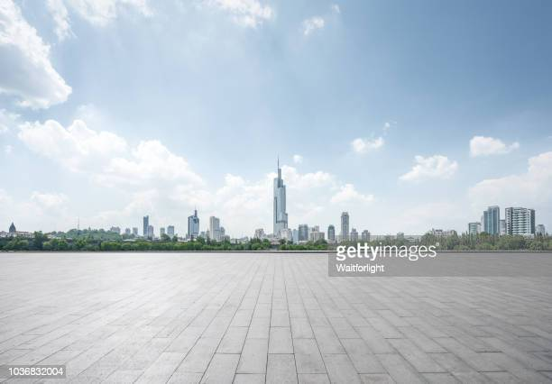 empty parking lot with cityscape background - street stockfoto's en -beelden