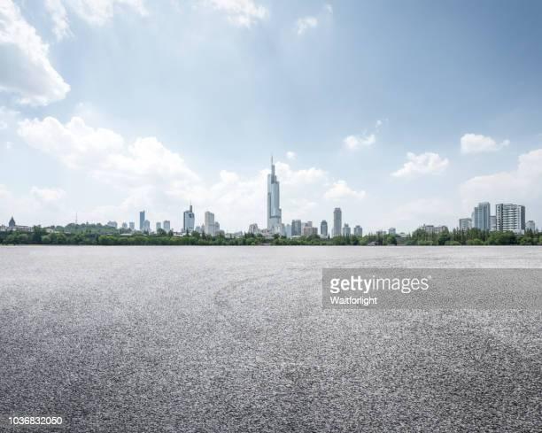 empty parking lot with cityscape background - nanjing road stockfoto's en -beelden