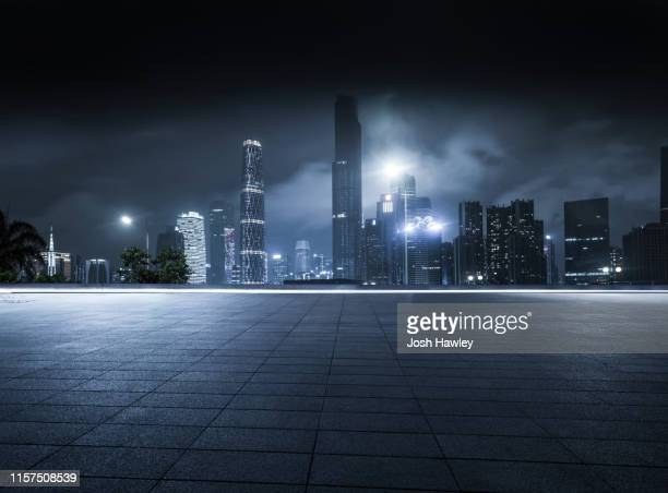 empty parking lot with cityscape background - city night stock pictures, royalty-free photos & images