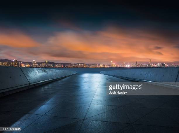 empty parking lot with cityscape background - urban road stock pictures, royalty-free photos & images