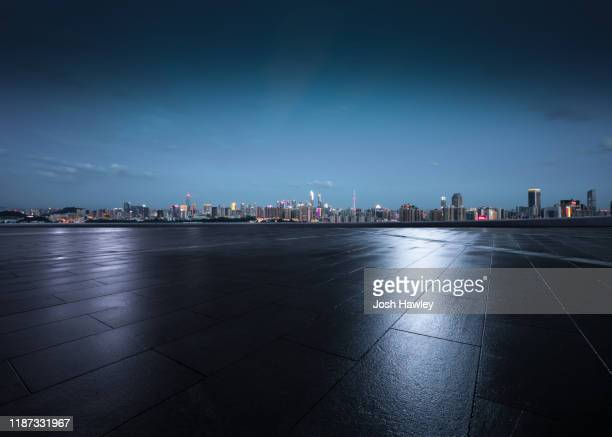 empty parking lot with cityscape background - empty lot night stock pictures, royalty-free photos & images