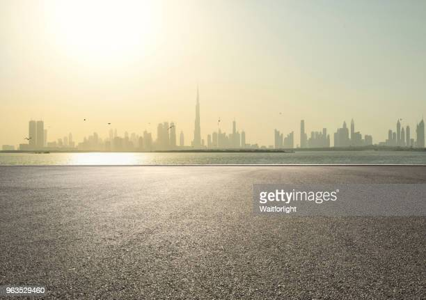 empty parking lot with dubai skyline background - thoroughfare stock pictures, royalty-free photos & images