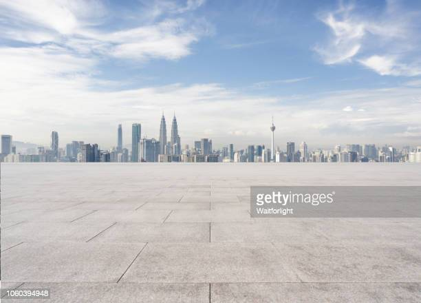 empty parking lot with kuala lumpur skyline background - kuala lumpur stock pictures, royalty-free photos & images