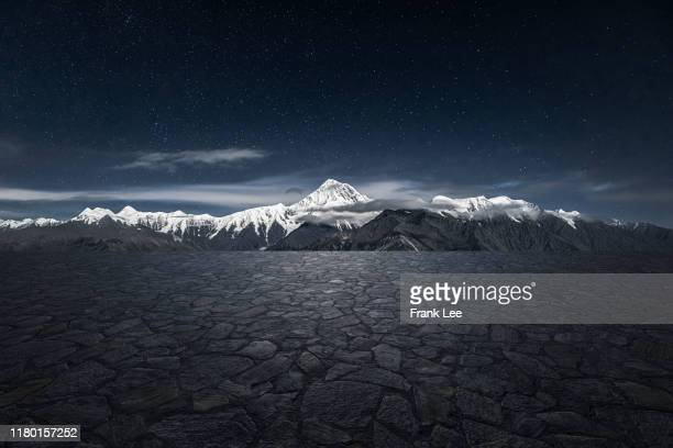 empty parking lot with snowcapped mountain background - empty lot night stock pictures, royalty-free photos & images