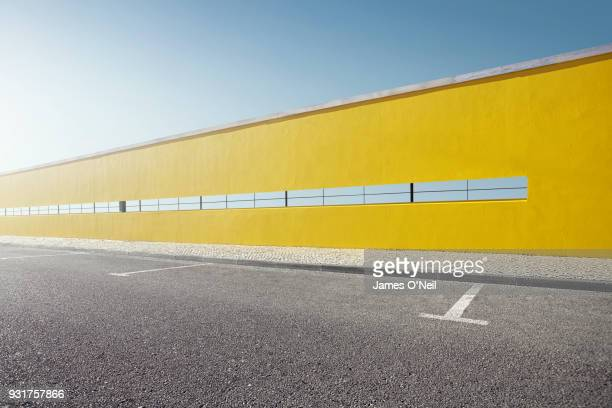 empty parking spaces in front of yellow wall. - car park stock pictures, royalty-free photos & images