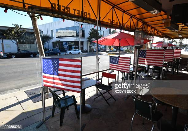 Empty patio tables separated by plastic dividers adorned with American flags are seen at Mel's drive-in diner in West Hollywood, California on...