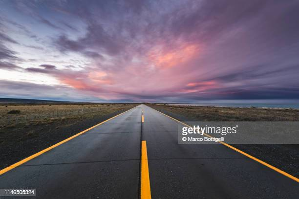 empty paved road at sunset in the chilean patagonia - horizont stock-fotos und bilder