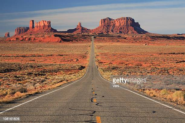 Empty paved road leading to Monument Valley