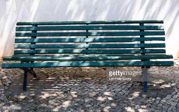 empty pavement bench in shadows - lyn holly coorg stockfoto's en -beelden