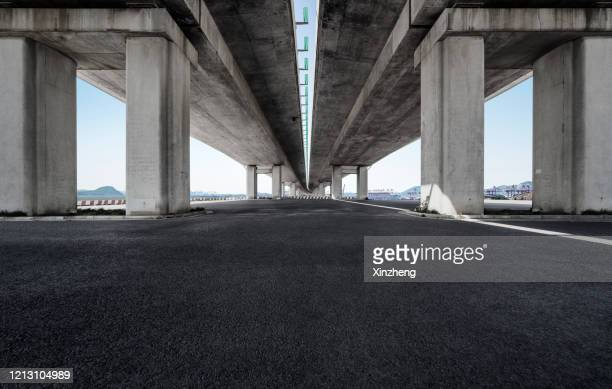 empty pavement under highway bridges - symmetry stock pictures, royalty-free photos & images