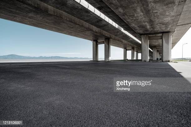 empty pavement under highway bridges - paved driveway stock pictures, royalty-free photos & images