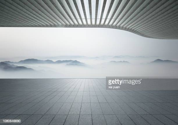 empty pavement with misty mountains - architecture stock pictures, royalty-free photos & images