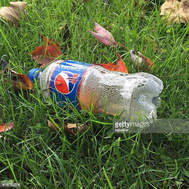 empty pepsi plastic soda bottle on grass - soda bottle stock photos and pictures