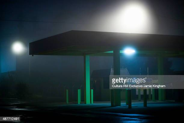 Empty petrol station in mist at night