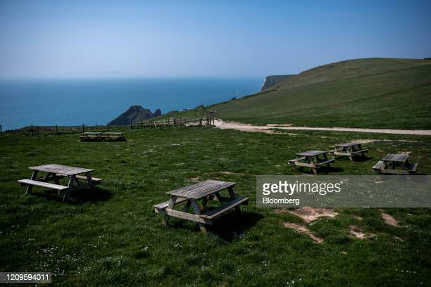 Empty picnic benches stand next to a footpath which leads down to the beach during the national lockdown on Easter weekend in Durdle Door UK on...