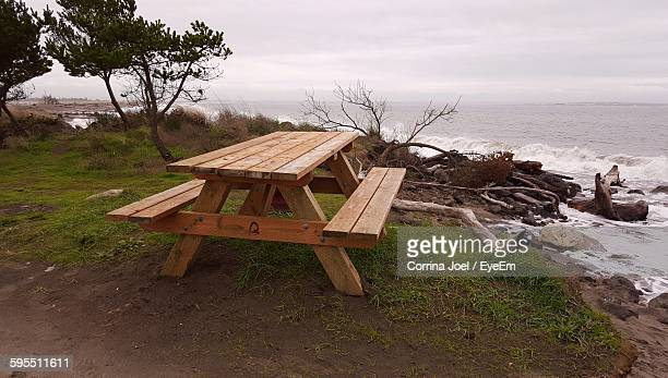empty picnic table at sea shore against cloudy sky - picnic table stock pictures, royalty-free photos & images