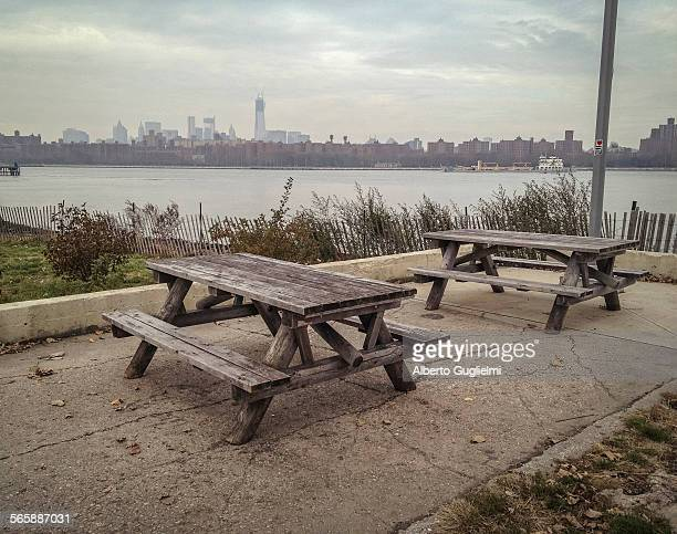 Empty picnic tables in urban park at waterfront