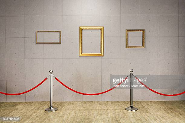 Empty picture frames behind velvet rope