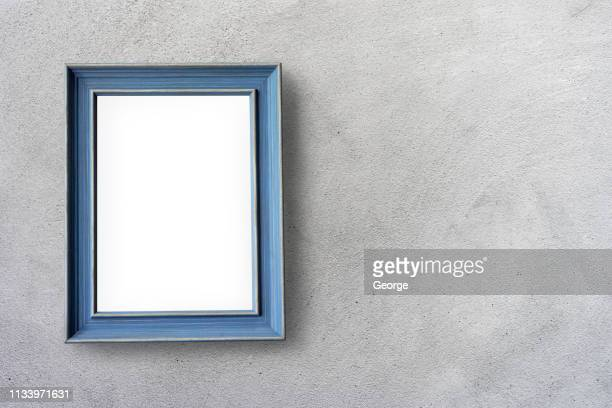 empty picture frames hanging on cement wall - george wood stock pictures, royalty-free photos & images
