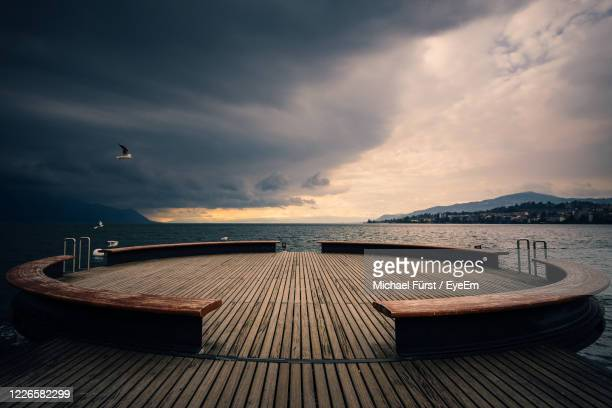 empty pier over sea against sky at sunset - vaud canton stock pictures, royalty-free photos & images