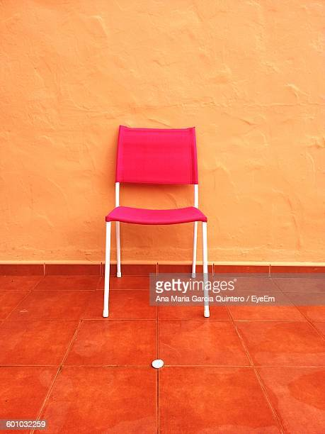 Empty Pink Chair On Tiled Floor Against Orange Wall At Home