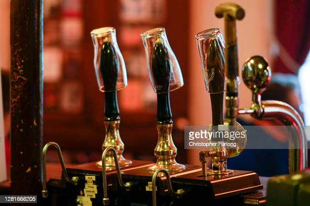 Empty pint glasses sit on the top of beer pumps of the Peveril Of The Peak pub, signifying they have been disconnected from the barrels ahead of new...