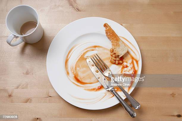 Empty plate and cup after breakfast, overhead view