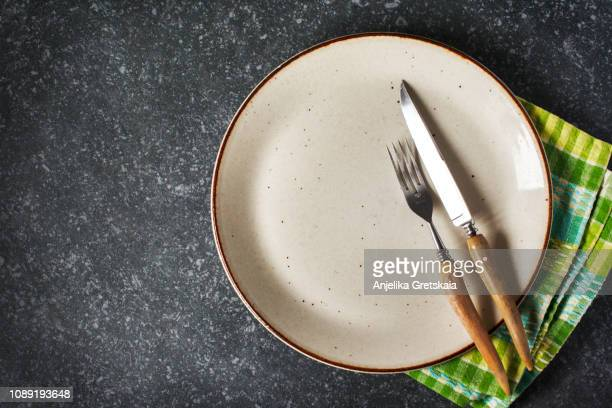 empty plate and fork and knife with napkin on dark grey stone background - 盛り皿 ストックフォトと画像