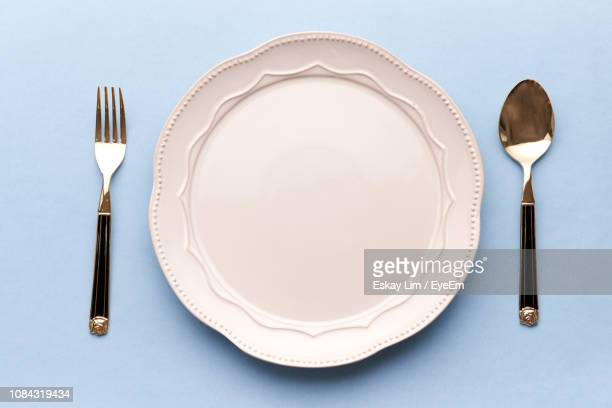 empty plate and fork with spoon against blue background - plate stock pictures, royalty-free photos & images