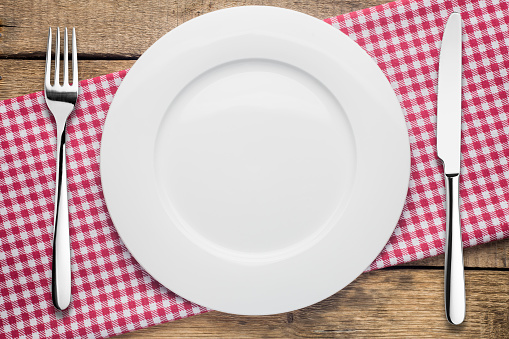 empty plate on a wooden background, a napkin in a red and white 1002864154