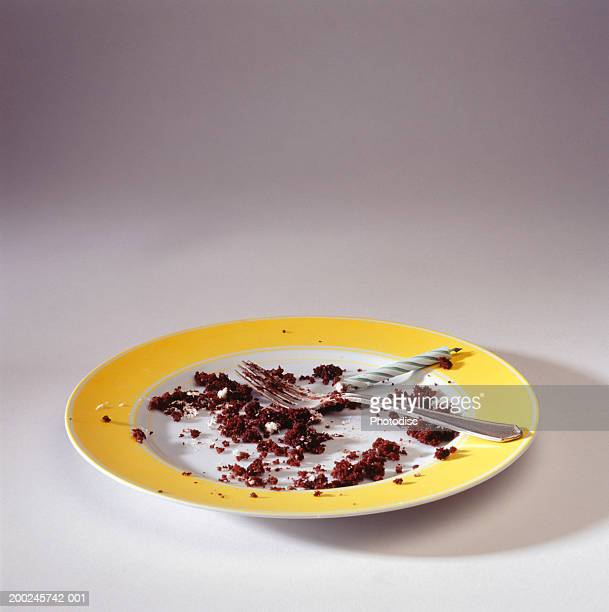 Empty plate with crumbs and candle, elevated view