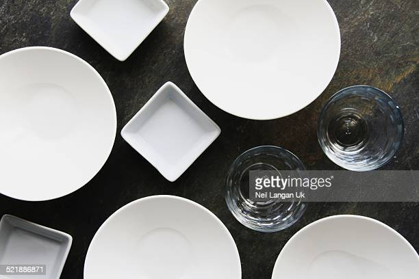 empty plateds and glasses on slate background