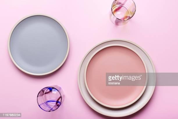empty plates and drinking glasses on pink background - teller stock-fotos und bilder