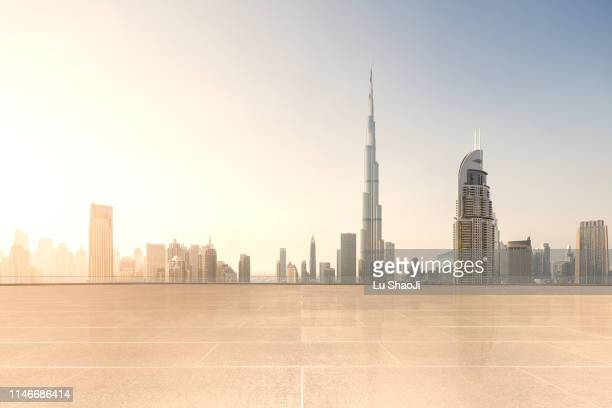 empty platform with city skyline and cityscape at sunset in dubai.uae - international landmark stock pictures, royalty-free photos & images