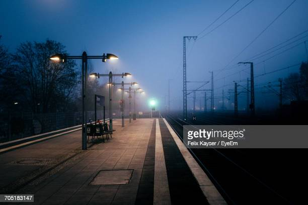 Empty Railroad Station During Foggy Weather At Dusk