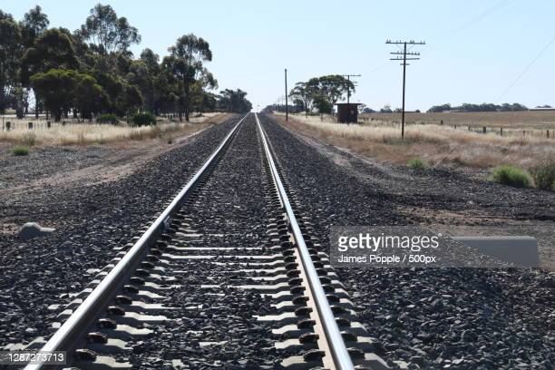 empty railroad tracks against clear sky,nelson st,nhill vic,australia - james popple stock pictures, royalty-free photos & images