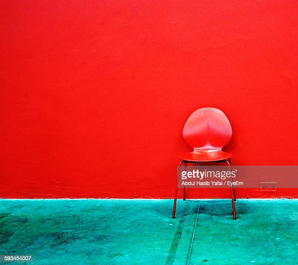 Empty Red Chair On Footpath Against Wall