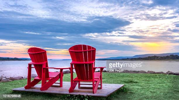 Empty red chairs and a sun set.