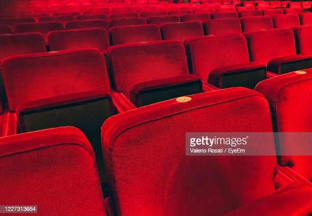 empty red velvet armchairs illuminated inside a concert hall - theatrical performance stock pictures, royalty-free photos & images