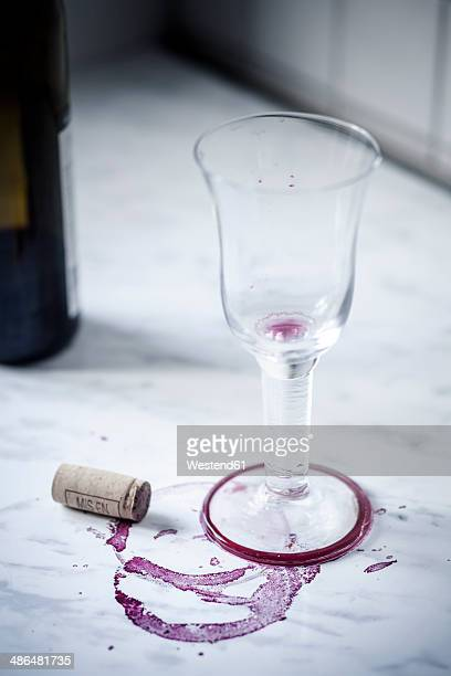 Empty red wine glass, bottle, stains and wine cork on white marble