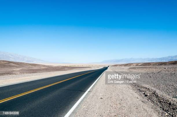 empty road against clear blue sky - double yellow line stock photos and pictures
