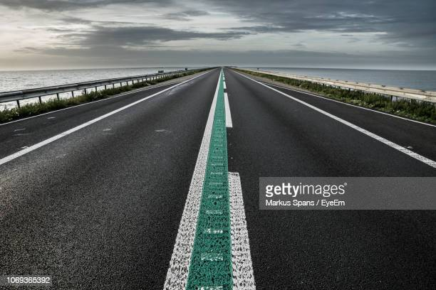empty road against cloudy sky during sunset - empty road stock pictures, royalty-free photos & images