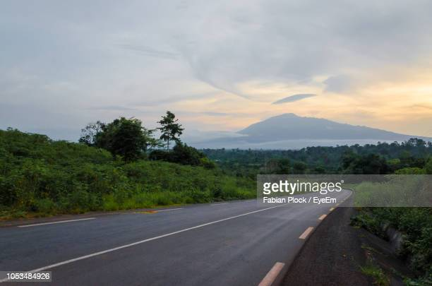 empty road against sky with mount cameroon in background - cameroon stock pictures, royalty-free photos & images