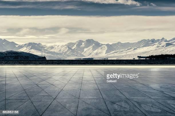 empty road against snowcapped mountain - rivage photos et images de collection