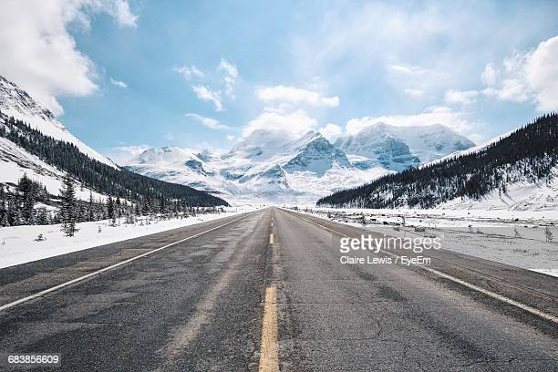 Empty Road Against Snowcapped Mountains